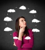 Νέα γυναίκα που σκέφτεται με την κυκλοφορία σύννεφων γύρω από το κεφάλι της Στοκ Εικόνες