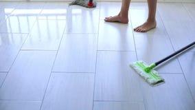 Νέα γυναίκα που σκουπίζει το άσπρο πάτωμα κεραμιδιών με τη σφουγγαρίστρα στο σπίτι απόθεμα βίντεο