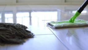 Νέα γυναίκα που σκουπίζει το άσπρο πάτωμα κεραμιδιών με τη σφουγγαρίστρα στο σπίτι φιλμ μικρού μήκους