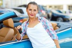 Νέα γυναίκα που στέκεται κοντά σε έναν μετατρέψιμο με τα κλειδιά διαθέσιμα Στοκ Εικόνες