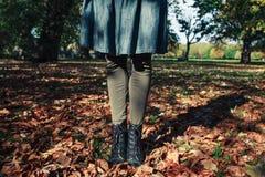Νέα γυναίκα που στέκεται στα φύλλα Στοκ Φωτογραφίες