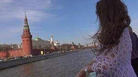 Νέα γυναίκα που στέκεται στη γέφυρα της βάρκας που περνά τη Μόσχα Κρεμλίνο απόθεμα βίντεο
