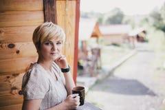 Νέα γυναίκα που στέκεται στο άνετο μπαλκόνι με ένα φλυτζάνι του τσαγιού Στοκ φωτογραφία με δικαίωμα ελεύθερης χρήσης