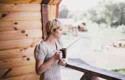 Νέα γυναίκα που στέκεται στο άνετο μπαλκόνι με ένα φλυτζάνι του τσαγιού Στοκ φωτογραφίες με δικαίωμα ελεύθερης χρήσης
