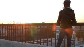 Νέα γυναίκα που στέκεται στο ηλιοβασίλεμα προσοχής γεφυρών στεγών στην πόλη φιλμ μικρού μήκους