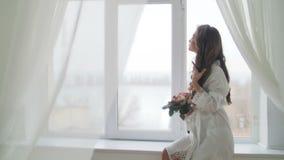Νέα γυναίκα που στέκεται στο παράθυρο φιλμ μικρού μήκους