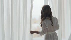 Νέα γυναίκα που στέκεται στο παράθυρο απόθεμα βίντεο