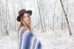 Νέα γυναίκα που στέκεται στο χιόνι με το Βοημίας καπέλο και το κάλυμμα ύφους Στοκ Εικόνες