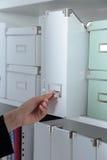 Νέα γυναίκα που στέκεται την επόμενη ντουλάπα με τους φακέλλους Στοκ φωτογραφία με δικαίωμα ελεύθερης χρήσης