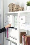 Νέα γυναίκα που στέκεται την επόμενη ντουλάπα με τους φακέλλους Στοκ Εικόνες