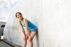 Νέα γυναίκα που στηρίζεται μετά από το τρέξιμο από τον τοίχο στην πόλη με το μεγάλο χαμόγελο στοκ εικόνα με δικαίωμα ελεύθερης χρήσης