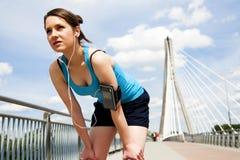 Νέα γυναίκα που στηρίζεται μετά από το τρέξιμο μπλε sportswear πέρα από τον ουρανό Στοκ εικόνες με δικαίωμα ελεύθερης χρήσης