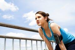 Νέα γυναίκα που στηρίζεται μετά από το τρέξιμο μπλε sportswear πέρα από τον ουρανό Στοκ Εικόνες