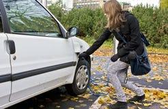 Νέα γυναίκα που συνδέει σε ένα ηλεκτρικό αυτοκίνητο Στοκ Εικόνες