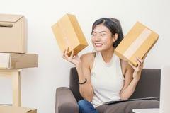 Νέα γυναίκα που συσκευάζει και που κινεί το σπίτι τους, συσκευασία on-line μάρκετινγκ και παράδοση, στοκ φωτογραφίες