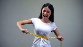 Νέα γυναίκα που σφίγγει μετρώντας την ταινία, που βασανίζεται με τη διατροφή, βουλιμία στοκ εικόνα