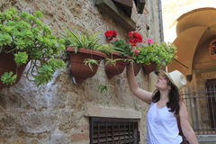 Νέα γυναίκα που σφυρίζει και που εξετάζει τα λουλούδια Στοκ φωτογραφία με δικαίωμα ελεύθερης χρήσης