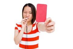 Νέα γυναίκα που σφυρίζει και που παρουσιάζει κόκκινη κάρτα Στοκ Εικόνες