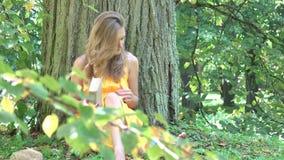 Νέα γυναίκα που τελειώνουν διαβάζοντας το βιβλίο κάτω από τον παχύ κορμό δέντρων 4K απόθεμα βίντεο