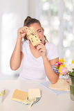 Νέα γυναίκα που τιτιβίζει μέσω ενός τυριού με τις τρύπες Στοκ Εικόνα