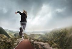 Νέα γυναίκα που τρέχει και που πηδά κοντά στα βουνά και τη λίμνη στοκ εικόνα