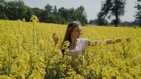 Νέα γυναίκα που τρέχει μέσω του κίτρινου τομέα σχετικά με τα λουλούδια HD απόθεμα βίντεο