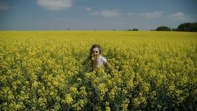 Νέα γυναίκα που τρέχει μέσω του κίτρινου τομέα σχετικά με τα λουλούδια HD φιλμ μικρού μήκους