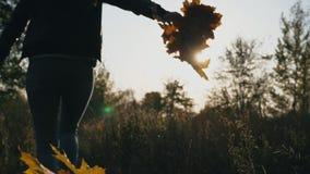 Νέα γυναίκα που τρέχει μέσω του πάρκου φθινοπώρου με την ανθοδέσμη των κίτρινων φύλλων σφενδάμου στο χέρι της Κορίτσι που έχει τη φιλμ μικρού μήκους
