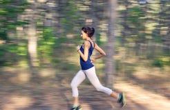 Νέα γυναίκα που τρέχει σε έναν αγροτικό δρόμο στο δάσος φθινοπώρου στοκ εικόνες