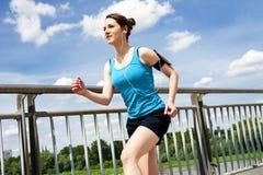 Νέα γυναίκα που τρέχει στην πόλη πέρα από το brige στο φως ήλιων, smil Στοκ Εικόνες