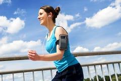 Νέα γυναίκα που τρέχει στην πόλη πέρα από το brige στο φως ήλιων, smil Στοκ φωτογραφία με δικαίωμα ελεύθερης χρήσης
