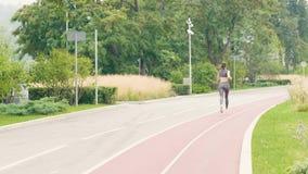 Νέα γυναίκα που τρέχει στο θερινό πάρκο στην πίσω άποψη σκουντημάτων πρωινού απόθεμα βίντεο