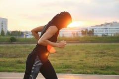 Νέα γυναίκα που τρέχει στο στάδιο υπαίθριο στο ηλιοβασίλεμα στοκ φωτογραφία