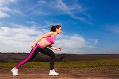Νέα γυναίκα που τρέχει στο υπόβαθρο μπλε ουρανού Στοκ Εικόνες