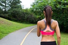 Νέα γυναίκα που τρέχει στο jogging ίχνος στοκ φωτογραφία
