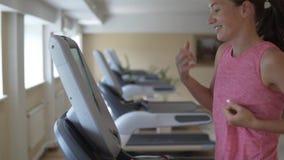 Νέα γυναίκα που τρέχει στο treadmill προσομοιωτή στη γυμναστική απόθεμα βίντεο