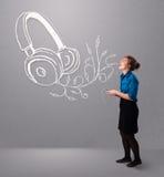 Νέα γυναίκα που τραγουδά και που ακούει τη μουσική με το αφηρημένο headpho Στοκ Εικόνες