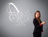 Νέα γυναίκα που τραγουδά και που ακούει τη μουσική με το αφηρημένο headpho Στοκ εικόνα με δικαίωμα ελεύθερης χρήσης