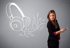 Νέα γυναίκα που τραγουδά και που ακούει τη μουσική με το αφηρημένο headpho Στοκ Φωτογραφίες