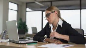 Νέα γυναίκα που τρυπιέται εργασία στον υπολογιστή στην αρχή, εξαντλημένος και unmotivated απόθεμα βίντεο