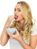 Νέα γυναίκα που τρώει ένα κύπελλο των καρυδιών Στοκ εικόνα με δικαίωμα ελεύθερης χρήσης