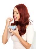 Νέα γυναίκα που τρώει τα καρύδια Στοκ Φωτογραφίες