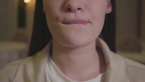 Νέα γυναίκα που τρώει τα νόστιμα τρόφιμα και που γλείφει τα χείλια της κοντά επάνω Χαμηλότερο σαγόνι του κοριτσιού που απολαμβάνε απόθεμα βίντεο