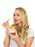 Νέα γυναίκα που τρώει τα πατατάκια πατατών Στοκ Φωτογραφίες
