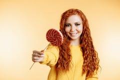 Νέα γυναίκα που τρώει την καραμέλα lollipop στοκ φωτογραφία