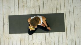 Νέα γυναίκα που τρώει την μπανάνα μετά από την κατηγορία γιόγκας Στοκ Φωτογραφίες