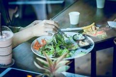 Νέα γυναίκα που τρώει τη σαλάτα και το ποτό στον καφέ Στοκ Φωτογραφίες