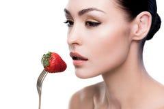 Νέα γυναίκα που τρώει τη φράουλα στο δίκρανο που απομονώνεται στο λευκό Στοκ φωτογραφία με δικαίωμα ελεύθερης χρήσης