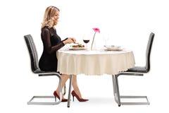 Νέα γυναίκα που τρώει το γεύμα μόνο στοκ φωτογραφία
