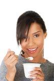 Νέα γυναίκα που τρώει το γιαούρτι ως υγιές πρόγευμα ή πρόχειρο φαγητό. Στοκ Φωτογραφία